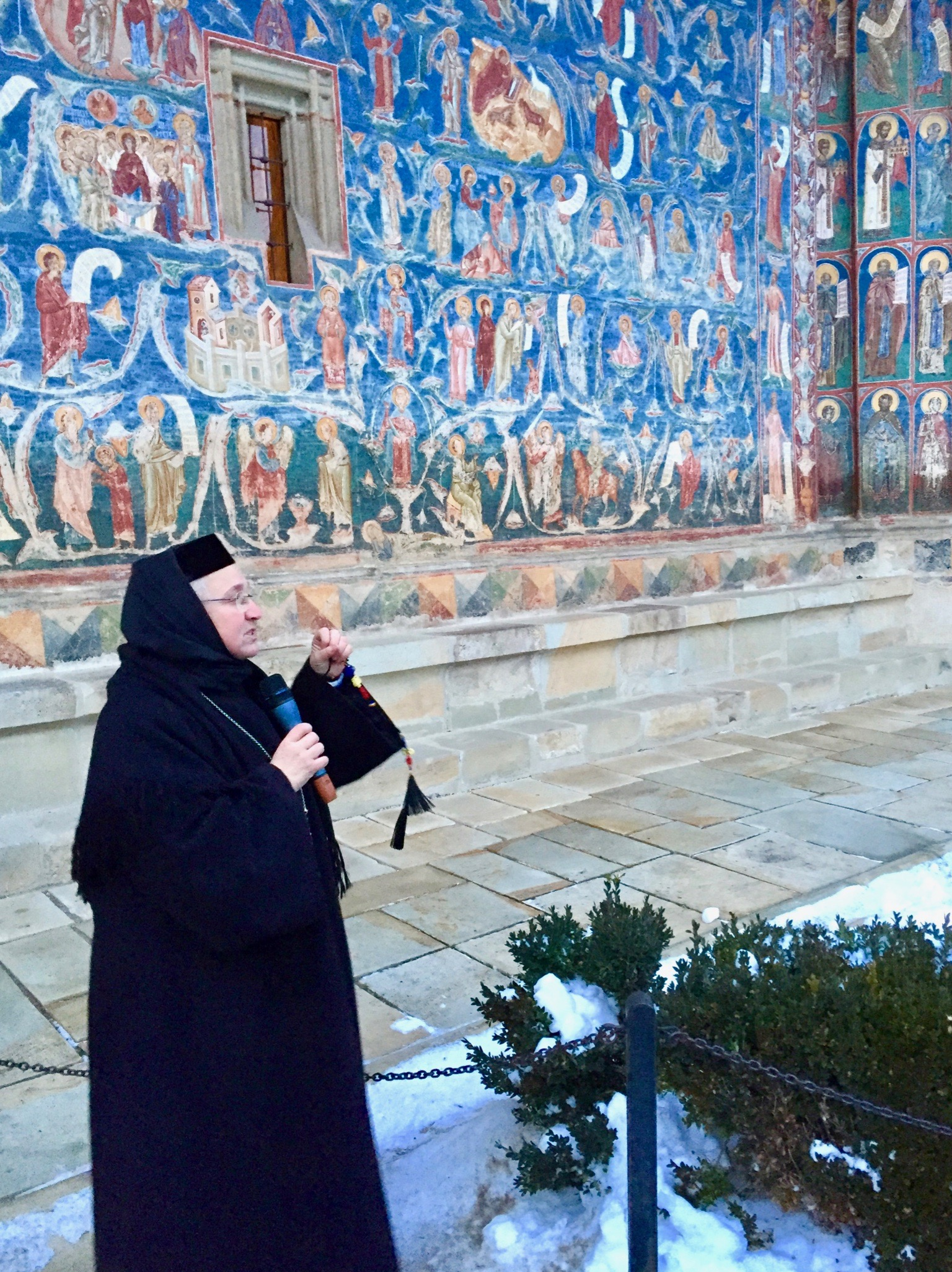 Nun in front of blue wall in Iasi, Romania