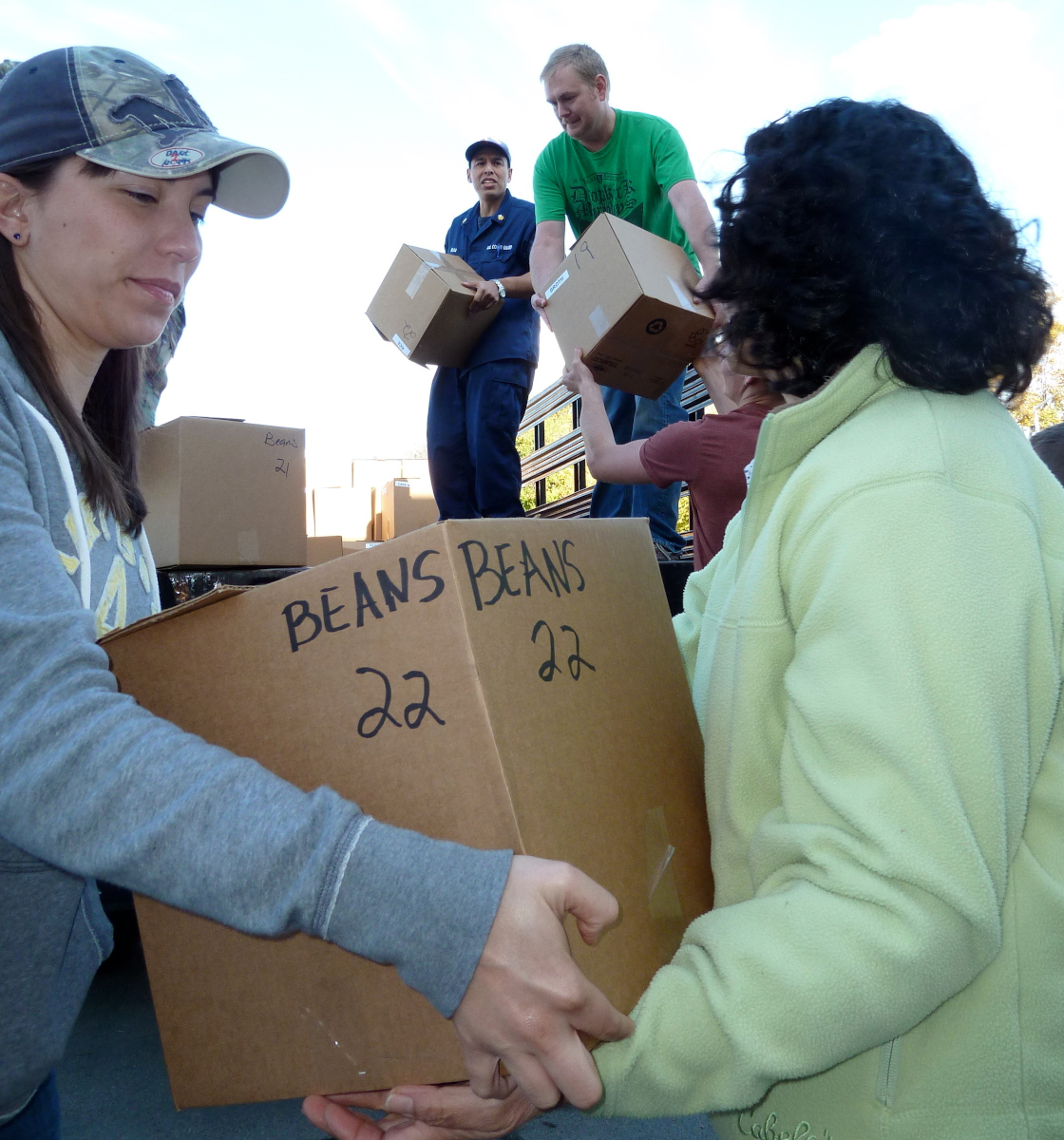 Food bank volunteers carrying boxes of canned beans